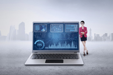 Female worker leans on laptop with chart