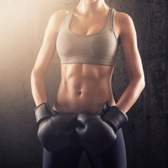 Strong athletic woman showing her abs and shaped stomach