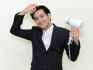 Asian handsome businessman with a hair dryer.