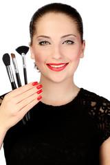 Молодая девушка с кистями для макияжа в руке