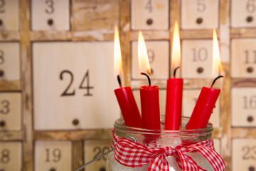 Vier brennende rote Kerzen zu Weihnachten mit Adventskalender