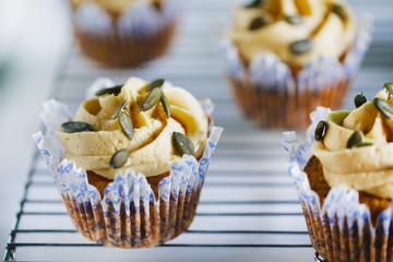Pumpkin cupcake with buttercream and pumpkin seeds, close-up