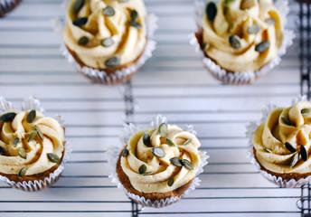 Pumpkin cupcake with buttercream and pumpkin seeds, fresh baking