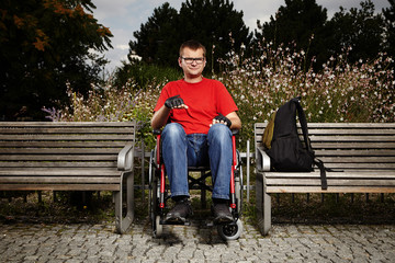 Young man on wheel chair - nice day in park