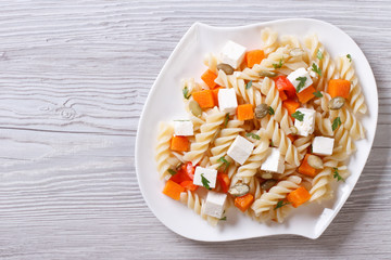 Pasta with pumpkin and feta on the table. top view