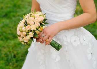 Wedding bouquet in hands of the bride with roses cream