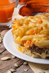 pasta baked with meat, cheese and pumpkin and juice. vertical