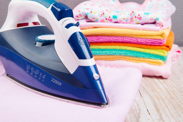 Steam iron and  with clothes, on bright background