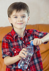 boy drinks water from a plastic bottle