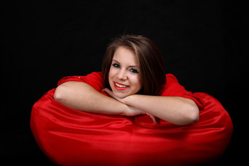 Uśmiechnięta dziewczyna na czerwonej poduszce.