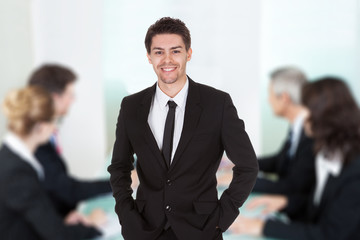 Businessman Standing Against Colleagues In Meeting At Office