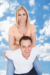 Happy Man Giving Piggyback Ride To Woman Against Sky