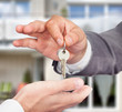 Property Agent Giving Keys To Owner Against New House