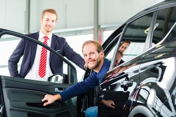 Verkäufer und Kunde mit Neuwagen von Autohaus