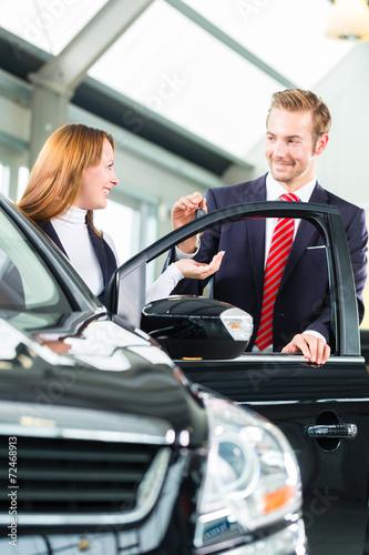 Verkäufer und Kundin mit Auto im Autohaus - 72468913
