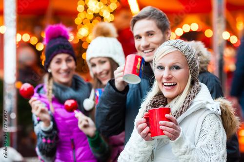 Leinwandbild Motiv Freunde, Glühwein und Kandisäpfel auf Weihnachtsmarkt