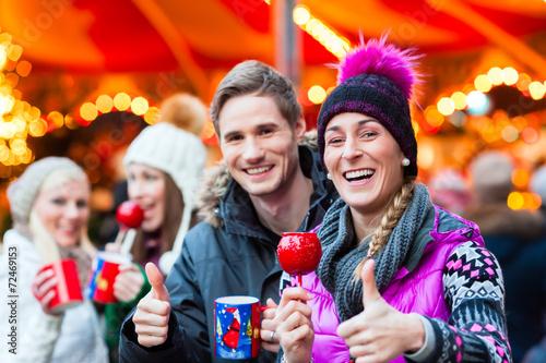 Leinwanddruck Bild Freunde, Glühwein und Kandisäpfel auf Weihnachtsmarkt
