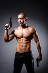 Ripped man with gun against grey background