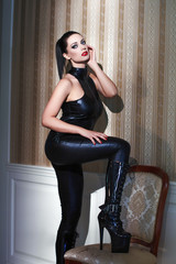 Sensual woman in latex catsuit posing at vintage wall