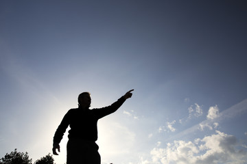 Backlit of a man pointing towards the horizon
