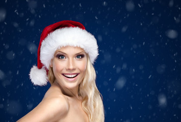 Beautiful woman in Christmas cap, blue snowy background