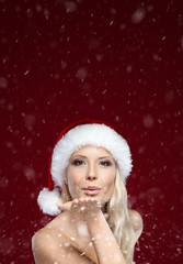 Beautiful woman in Christmas cap blows kiss