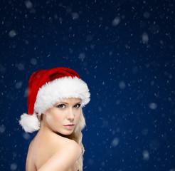 Pretty woman in Christmas cap, snowfall background