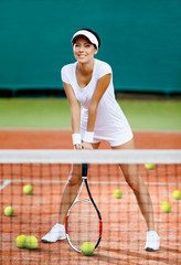 Pretty sportswoman at the tennis court with racquet
