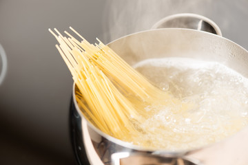 Pan with spaghetti cooking in boiling water