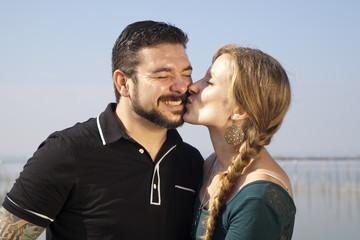 Mujer rubia con trenza besando a hombre con barba