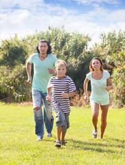 family of three running   at  park