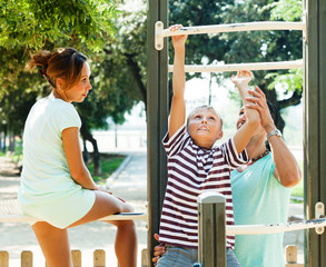 couple with  son training with chin-up bar
