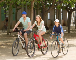 Happy family cycling in park togetherness