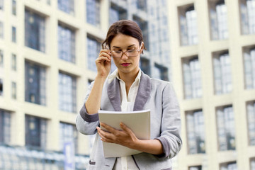 Business woman reading papers and holding glasses