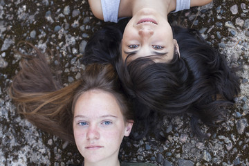 Two young girlfriend lying on a stone background.