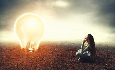 Woman is sitting on a ground and looking at lamp