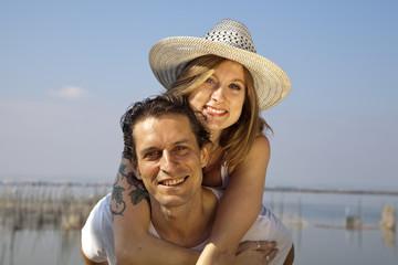Chica rubia con sombrero subida encima de su chico