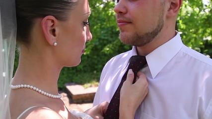 bride groom straightens tie