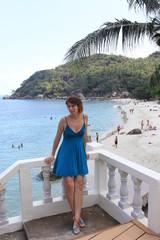 Girl sitting on the railing on sea background
