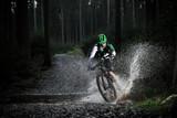 Fototapety Mountain biker speeding through forest stream.
