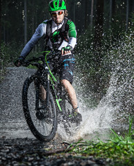 Mountain biker speeding through forest stream.