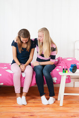 Teenager girl with grief sitting on bed