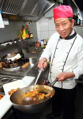 Asia Koch mit Wok beim Essen abfüllen