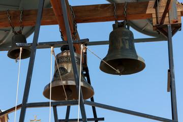 Three church bells in Greece against a blue sky