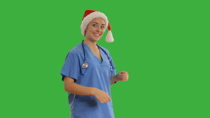 Charming young nurse dances and rejoices on the green screen