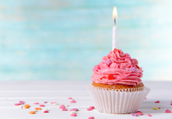Delicious birthday cupcake on table on light blue background