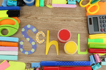 Inscription school lined of school supplies on wooden