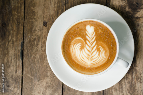 Fotobehang Cafe White cup of latte art coffee on grained wood top view