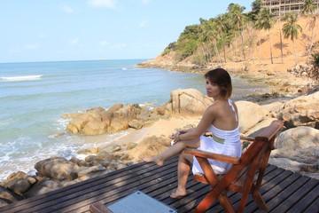 Woman sitting on beach-chair beside nice beach