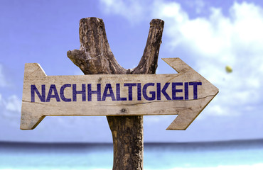 Sustainability (In German) wooden sign with a beach